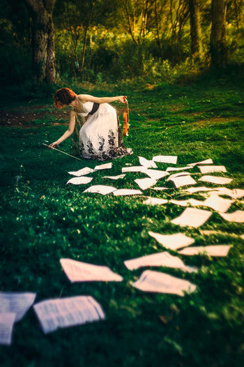 Woman Collecting Papers On Field