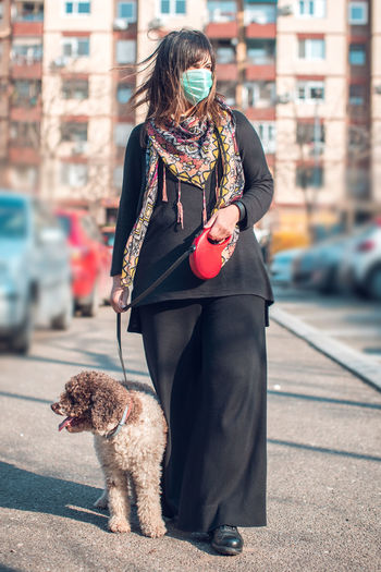 Woman with dog standing on street in city