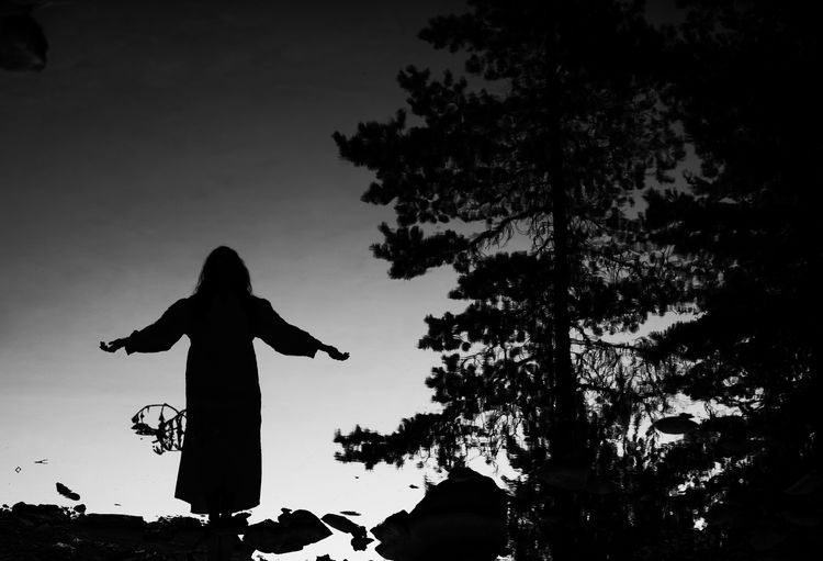 Silhouette woman with arms outstretched against sky during sunset