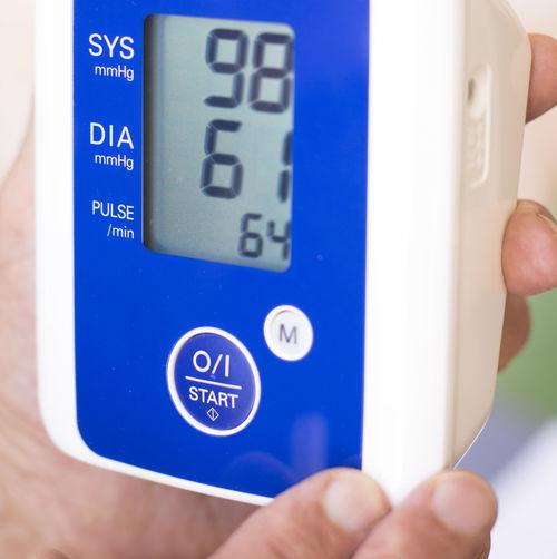 Cropped hand holding blood pressure gauge