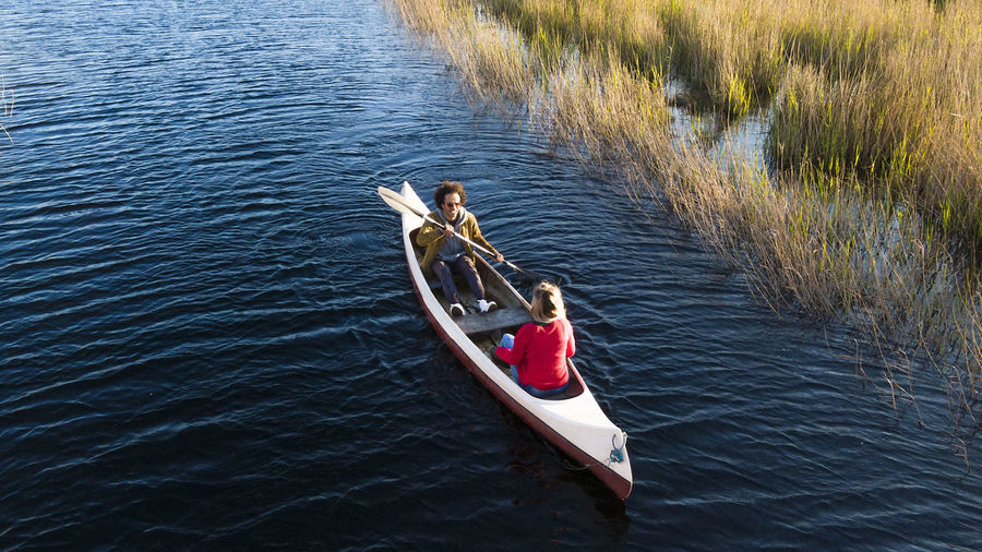 Rear view of women on boat in lake