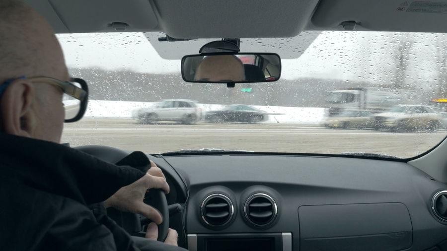 Reflection of car on wet windshield in rainy season
