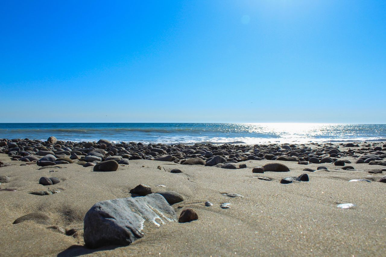 sea, horizon over water, beach, water, scenics, rock - object, blue, clear sky, nature, tranquil scene, beauty in nature, tranquility, day, no people, outdoors, sky, sunlight, sand