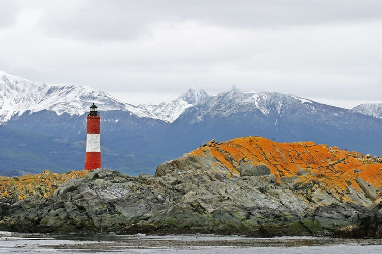 Lighthouse by snowcapped mountains against sky