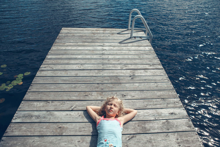 High angle view of girl relaxing on pier over water
