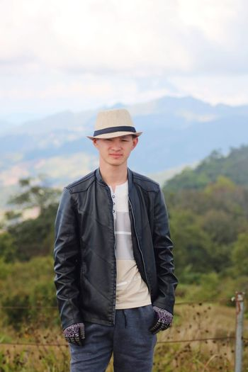 Young man wearing hat standing on land