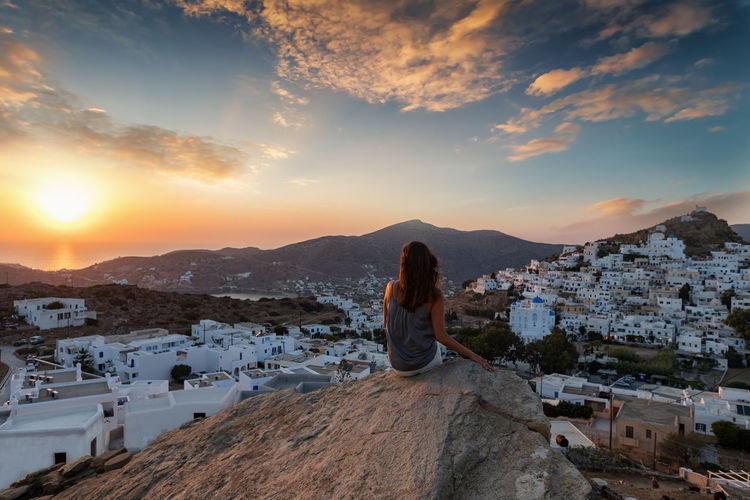 Rear view of woman looking at cityscape while sitting on rock against sky during sunset