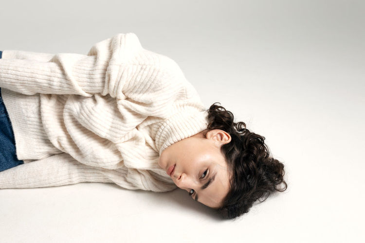 Portrait of woman lying down against white background