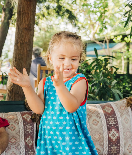Cute smiling girl clapping while standing in backyard