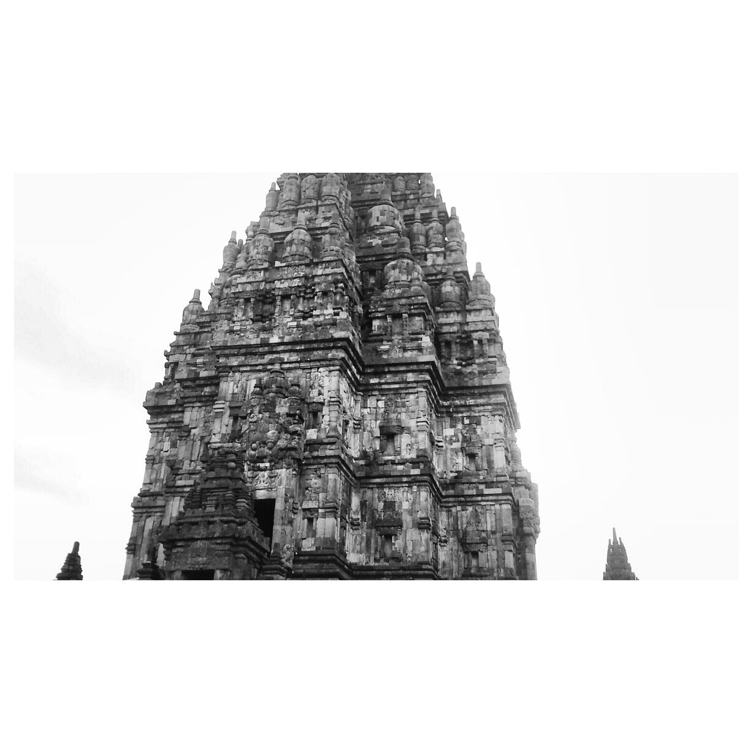 low angle view, clear sky, built structure, architecture, copy space, bird, history, building exterior, religion, transfer print, place of worship, animal themes, auto post production filter, sky, famous place, spirituality, ancient, sculpture, statue, outdoors