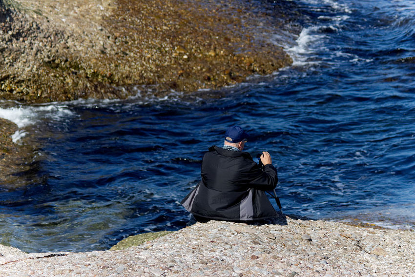 Man by the water getting ready to film Me Adult Adults Only Ankle Deep In Water Beauty In Nature Day Full Length Man Filming Men Men Filming Nature One Person Outdoors People Real People Rear View Rippled Rock - Object Sea Sitting Standing Water Wave