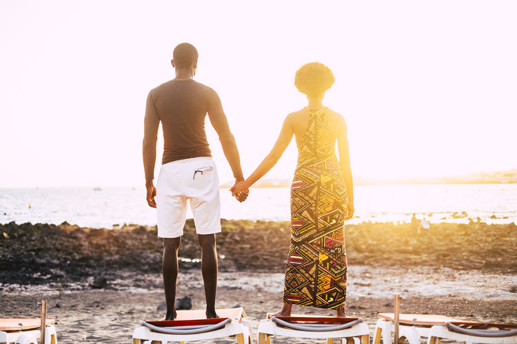 Romantic black couple in love african people looking at the sunset while stand up on a sun beads at the beach in summer holiday or sea lifestyle. People in romance leisure activity Rear View Water Real People Sky Togetherness Two People Standing Lifestyles Leisure Activity Beach Women Sea Men Nature Clear Sky Adult Casual Clothing Full Length Land Couple - Relationship Positive Emotion Outdoors Holiday Standing Sunbeam