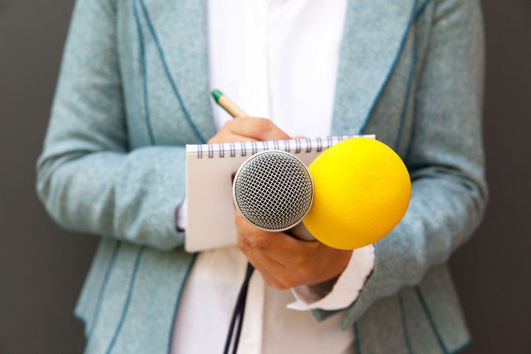 Midsection of journalist writing in book while holding microphones