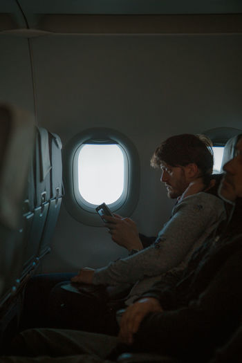 humans in transit People In Transit Transit Transportation Transitional Moments Stranger Real People Using Phone Reading Men Occupation Window Sitting Airplane Aircraft Aeroplane Airplane Seat Passenger Cabin The Traveler - 2018 EyeEm Awards