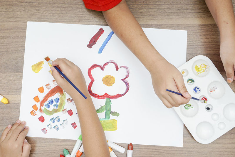 Art And Craft Kindergarten Paint Preschool Art And Craft Arts Culture And Entertainment Brushes Child Childhood Creativity Drawing - Activity Drawing - Art Product Education Finger Hand High Angle View Holding Human Body Part Human Hand Indoors  Leisure Activity Lifestyles One Person Paper Real People Table Women