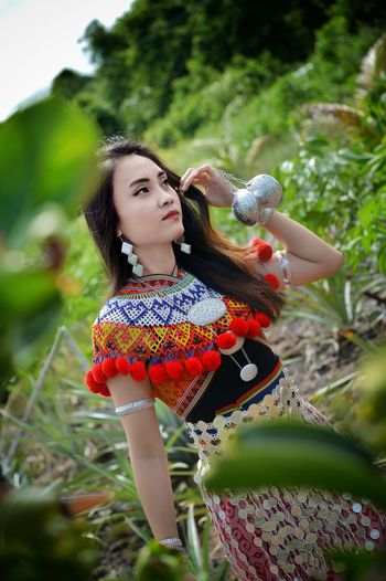 Close-up of woman wearing traditional clothes while standing amidst plants