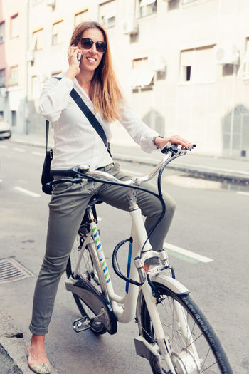 Woman talking over smart phone while riding bicycle on road