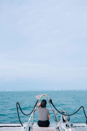 Rear view of woman on sea against sky