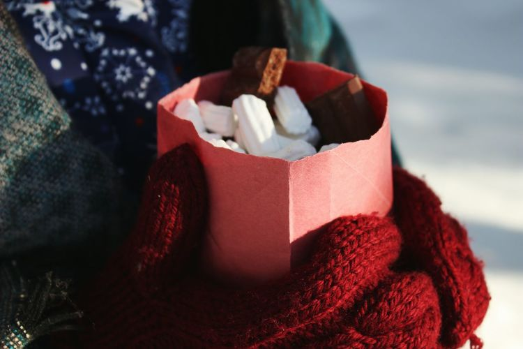 Midsection of person holding marshmallows in paper bag during winter