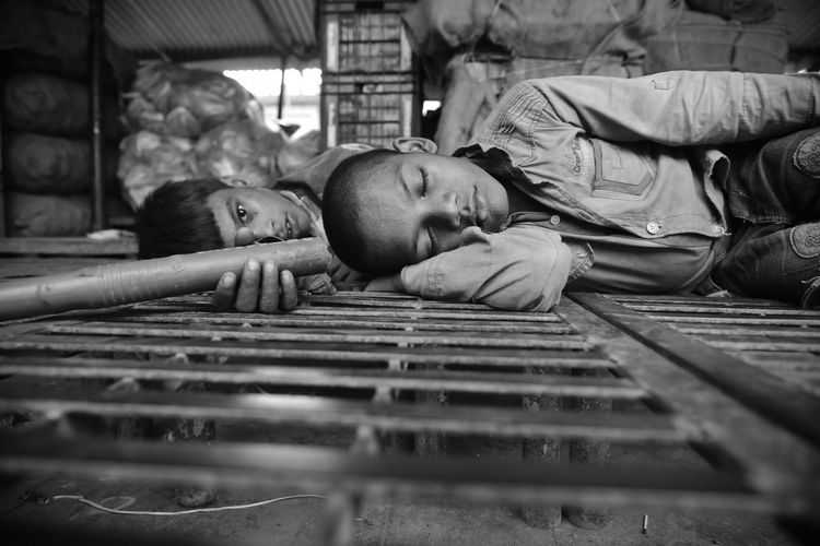 Surface Level Of Boys Lying On Metal Grate
