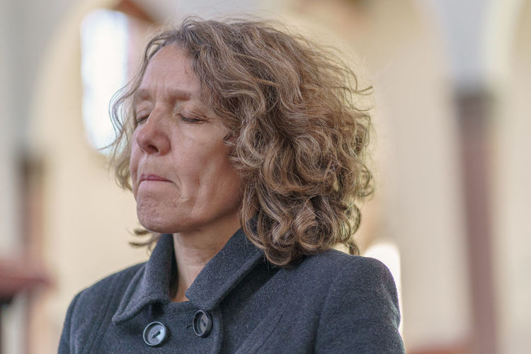 Close-up of woman praying with closed eyes in church