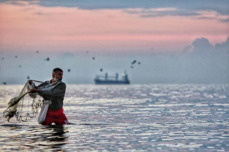 Mid adult man fishing in sea at sunset