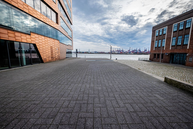 Surface level of footpath amidst buildings against sky