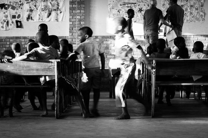 Africa Bench Blackandwhite Child Childhood Fun Game Indoors  Large Group Of People Playing Poor  Real People Running Rural School