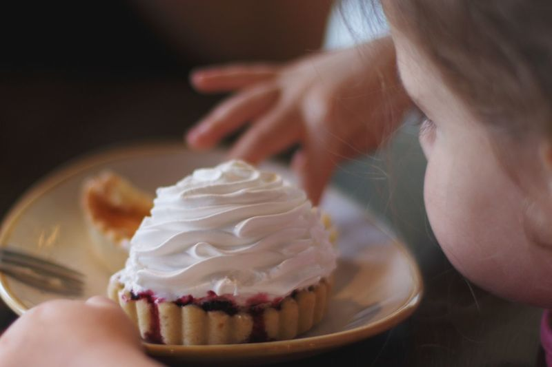 Close-up of girl's hand holding cupcake on table