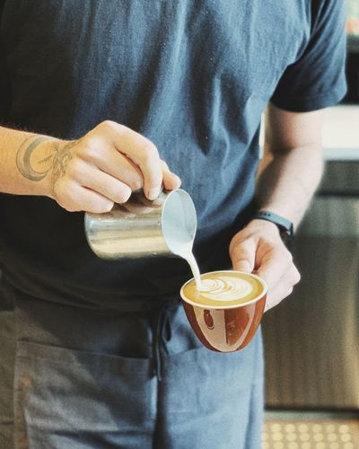 Midsection of man preparing coffee