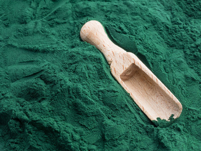 Wooden spoon on green powder