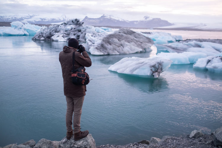Man standing in lake against sky during winter