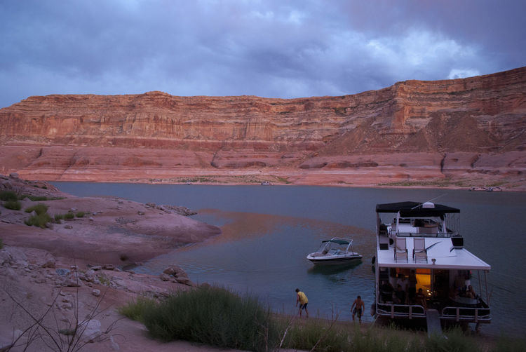 Ferry moored in lake powell by rocky mountains against cloudy sky