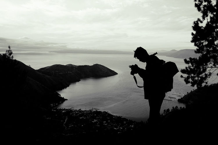 Silhouette man photographing sea against sky