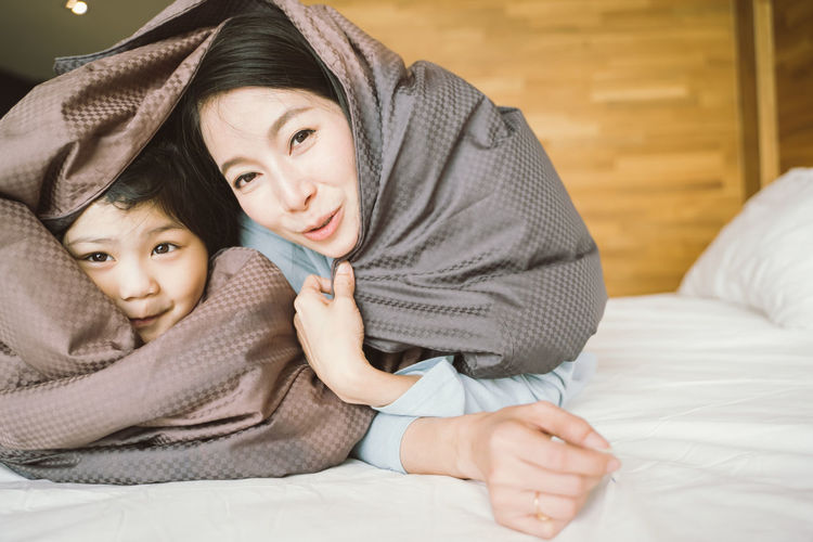 Mother and her daughter child girl playing in the bedroom and putting blanket on . Happy Asian family Asian  Family Happiness Happy Happy People Family Time Home House Daughter Parent Father Mother Dad Mom Love Lifestyles Living Room ASIA Japanese  Korean Thai Taiwan Bedroom Bed Kiss Smiling Smile Fun Portrait Girls Playing