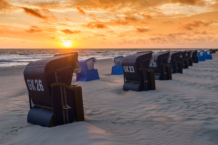 Hooded chairs at beach during sunset