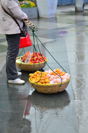 Low section of woman with fruits for sale at market stall