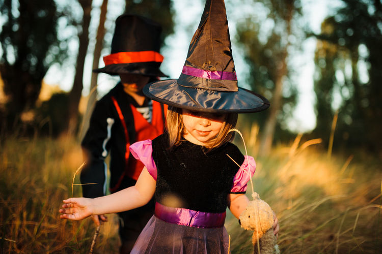 Girl with brother wearing costume during halloween at forest