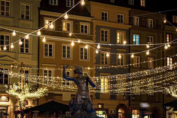 Statue against illuminated buildings in city at night