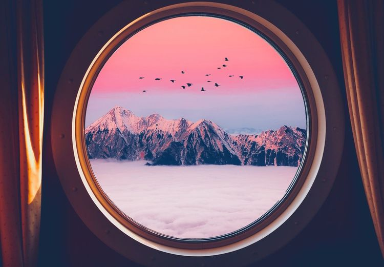 Scenic view of mountains seen through window during sunset