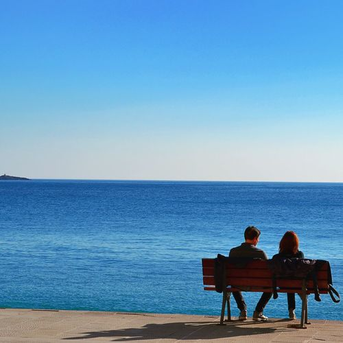 Rear view of couple sitting at beach against clear sky