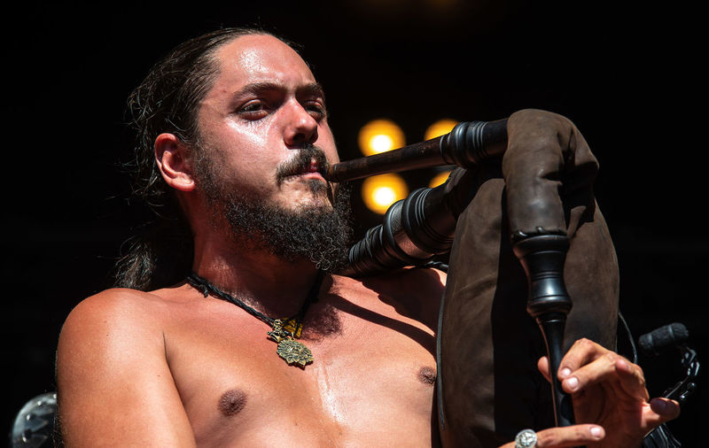 Close-Up Of Shirtless Man Playing Bagpipe During Concert