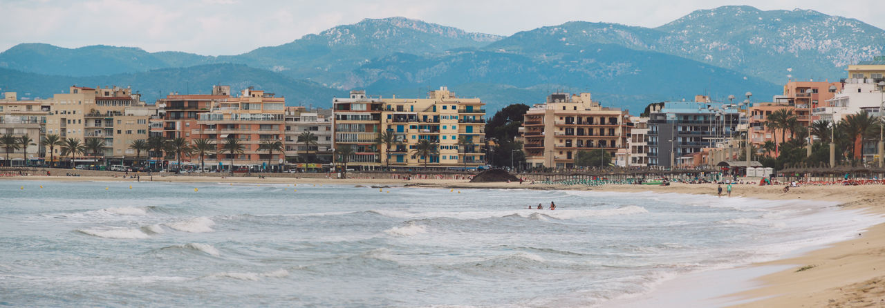 Panoramic View Of Beach With City In Background