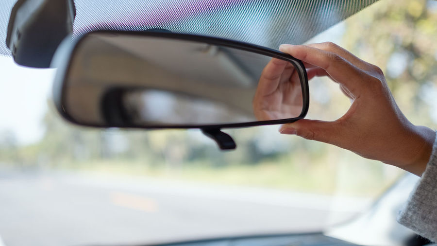 Close-up of hand adjusting rear-view mirror in car