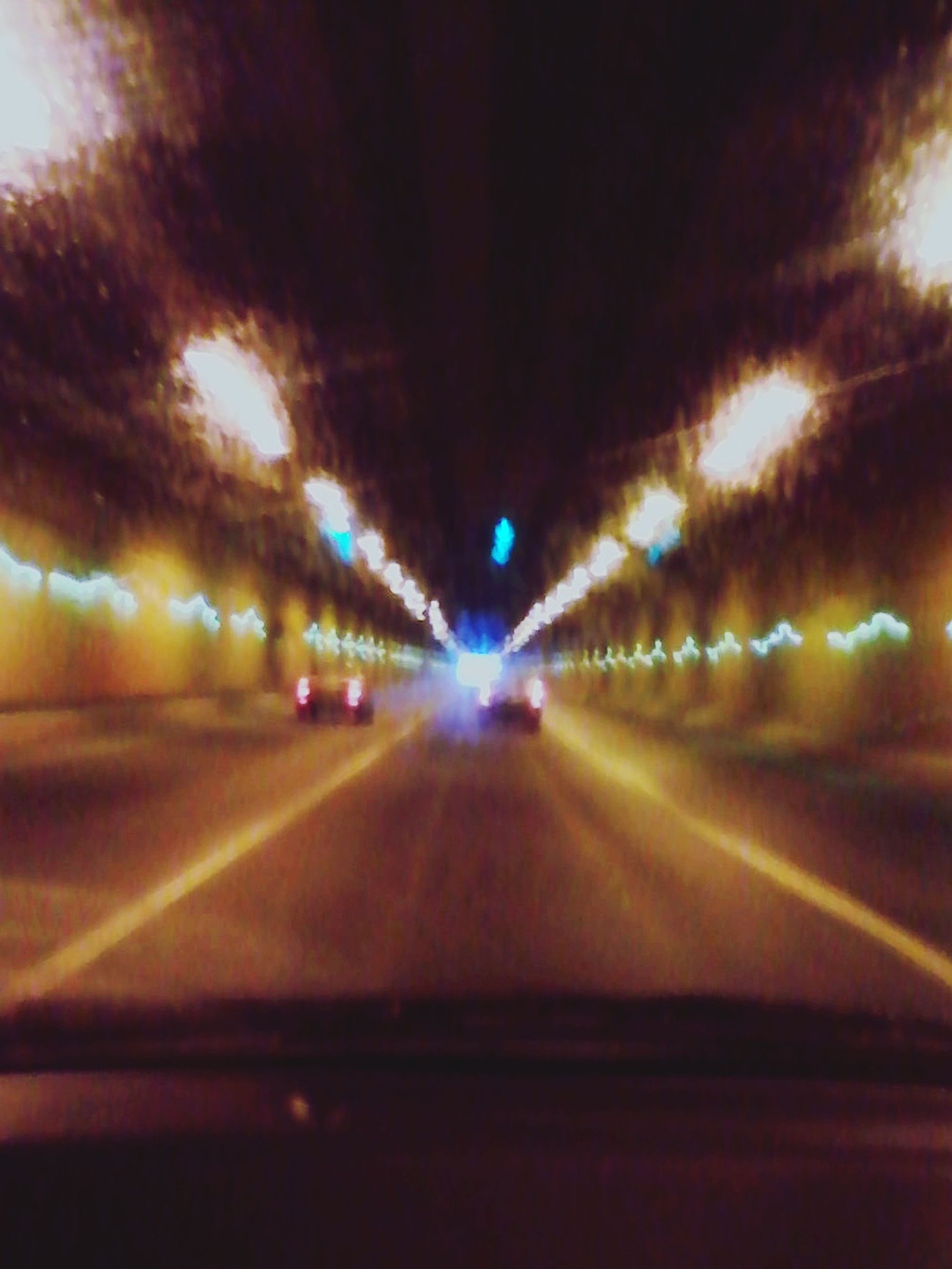 transportation, illuminated, the way forward, road, diminishing perspective, vanishing point, night, road marking, tunnel, indoors, blurred motion, lighting equipment, motion, windshield, sky, glass - material, light - natural phenomenon, car, mode of transport, no people