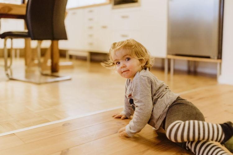 Portrait of girl sitting on hardwood floor at home