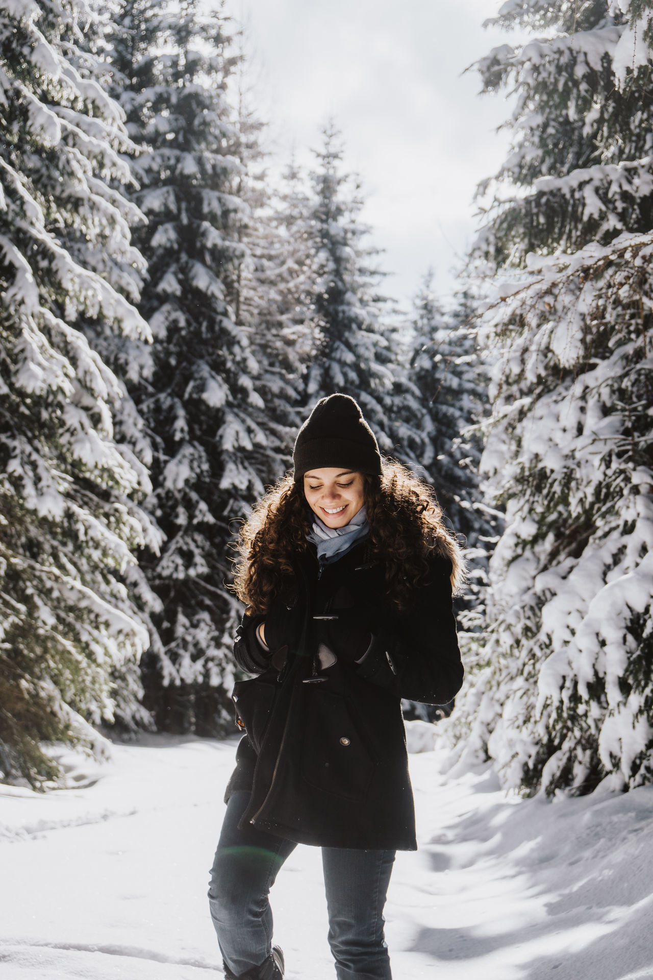 Smiling young woman in warm clothing standing amidst trees on snowy field