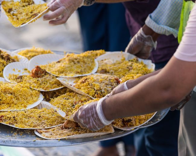 Midsection of people holding food at market stall