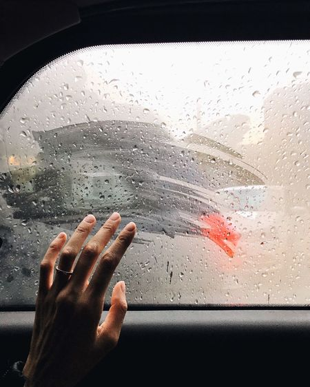 Cropped Image Of Hand Touching Wet Car Window