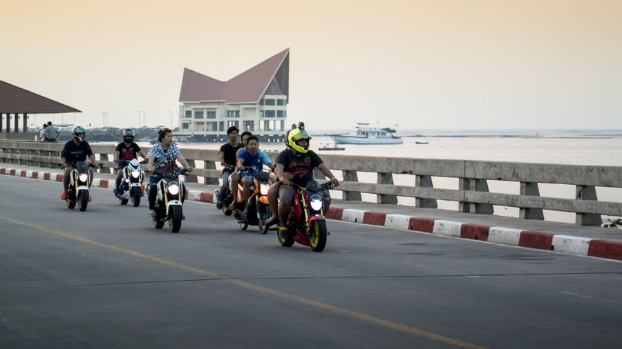 Group of teenager ride motorbike on bridge at sunset time Architecture Chon Buri City Life Clear Sky Group Of Objects Leisure Activity Lifestyles Men Motobikes Motorcycles Person Relaxing Ride Rider Sea Si Racha Spotted In Thailand Sriracha Street Teenager Transportation Traveling Water